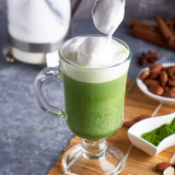 Matcha-latte-with-almond-milk-cream-glass-gray-stone-table_130040-1301